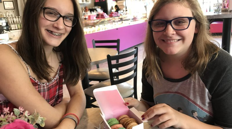 Two girls sitting with box of macarons