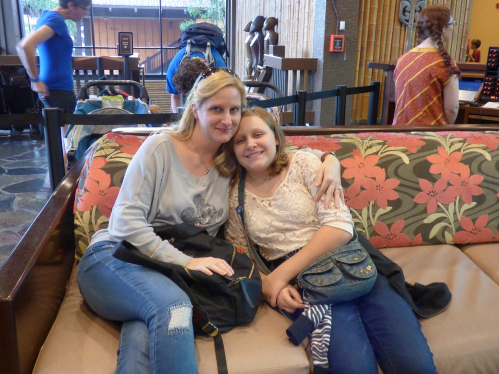 Mom and daughter sitting on couch at Polynesian Resort during Holiday hotel hopping at Disney's Bay Lake