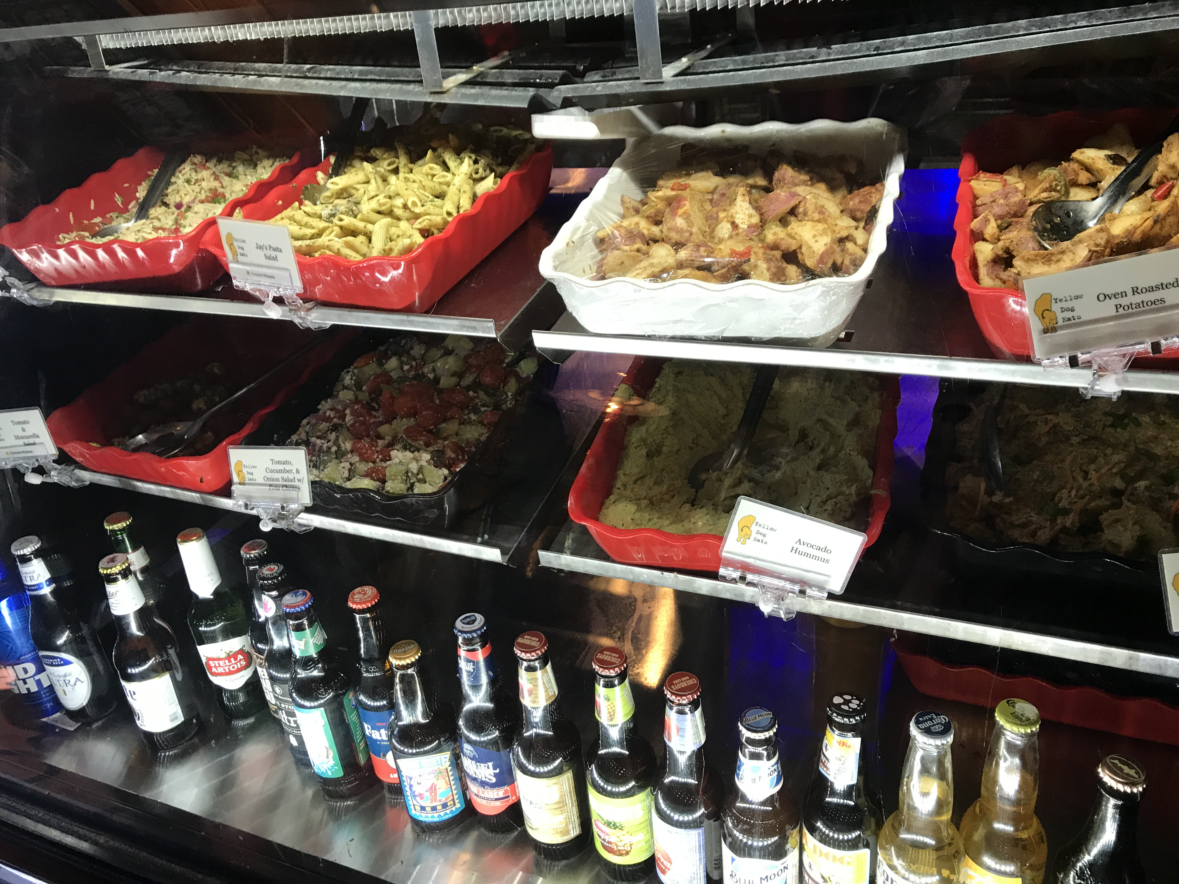 deli counter with sides and beer bottles
