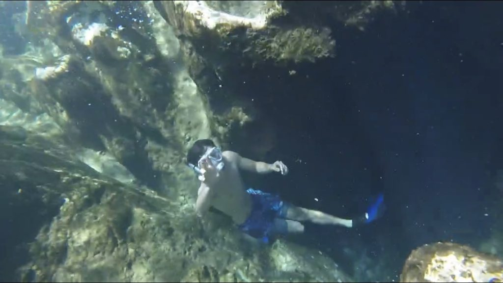 snorkeling boy waving to camera from deep rocky springs