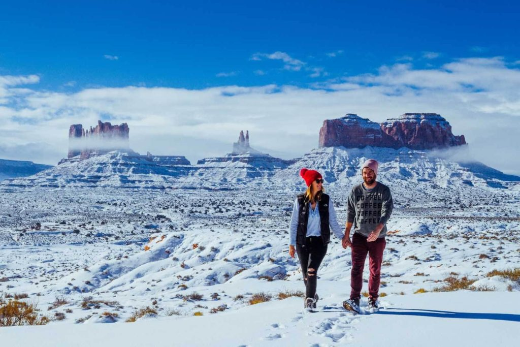 Man and woman holding hands walking through snow covered desert mountains