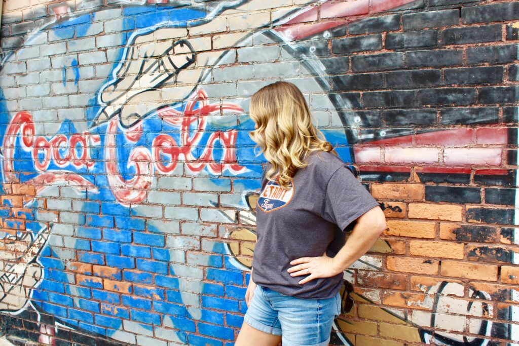 Woman standing by graffiti art wall