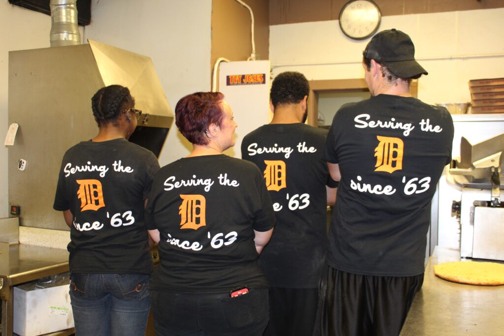 Dan & Vi's management team with back of shirts