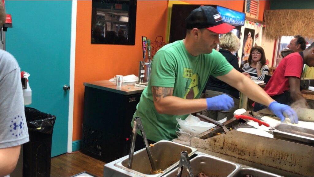 Owner of Papa Pineapples making food.