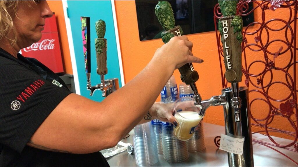 Woman filling beer glass from tap at Papa Pineapples